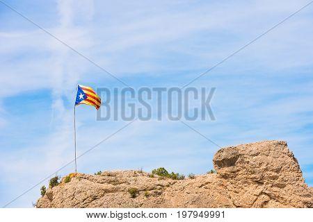 The Spanish Flag (estelada) On The Mountain, Over Blue Sky Background, Catalunya, Spain. Copy Space