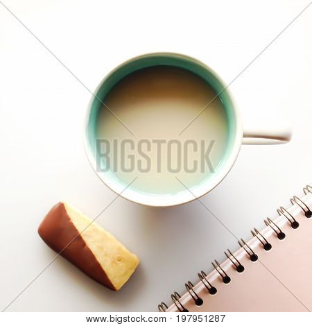 Taking a break from work with mug of tea chocolate-dipped shortbread cookie and notebook
