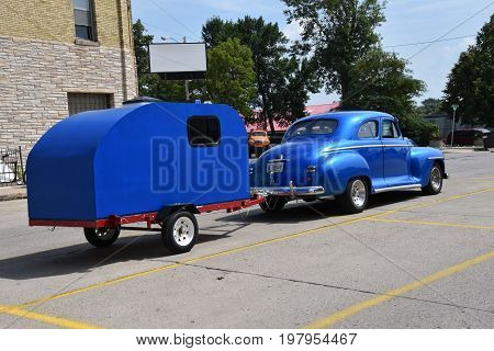 CASSELTON, NORTH DAKOTA, July 27, 2017: The annual Casselton Car Show which occurs the last Thursday of July features classic vehicles such as the restored 1948 Plymouth pulling a camper.