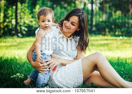 Young beautiful mother sitting with her child on a green grass and playing together