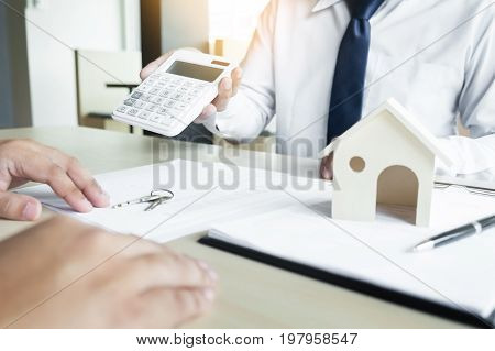 Real estate agent showing the purchase price on a calculator to his client