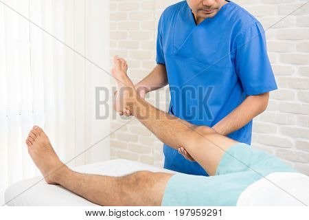 Physiotherapist training rehab exercise to broken leg patient in hospital