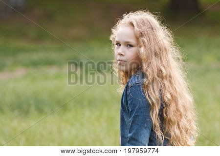 Little girl with curly hair feeling sadness - outdoor portrait, portrait