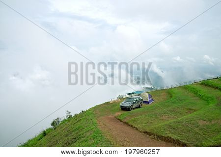 Phetchabun, Thailand - July17,2017 : Camping tent and dark grey car on mountain peak with view of mountain landscape waves of fog and cloudy sky at Phu Tub Berg Phetchabun province Thailand