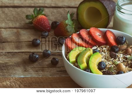 Muesli or granola on white bowl with fresh fruits nuts and cereal.Granola top with blueberries strawberries and avocado served with milk and honey for breakfast.Granola is healthy food for dieting.Granola or muesli on plank with copy space.