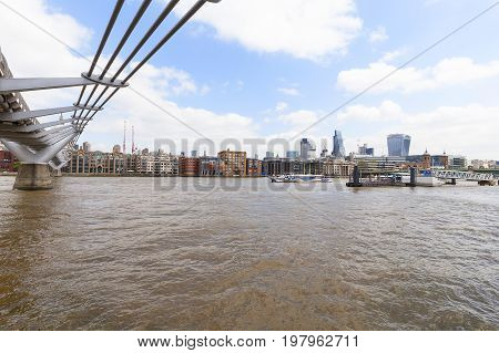 LONDON UNITED KINGDOM - JUNE 22 2017: Millennium Bridge and modern glazed office buildings. As of 2017 there are 17 skyscrapers in London that reach a roof height of at least 150 meters
