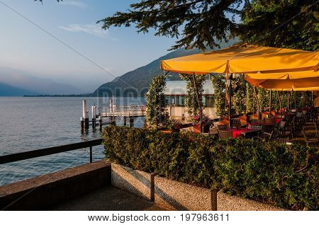 June 13th, 2017 - Lombardy, Italy. Waterfront restaurant in Bellano fishing village, situated on Como Lake shore. Cafe tables, lake and mountains view by sunset in small coast town Bellano.