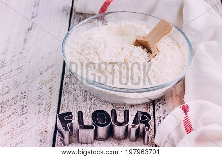 Flour in a glass bowl on a white wooden table background. Metal letters word Flour. Top view Copy space