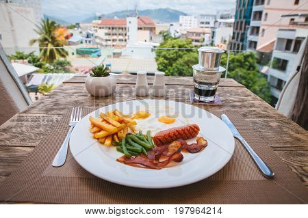 English breakfast with fried eggs, bacon, sausages, green beans and potato french fries on wooden table with beautiful city view