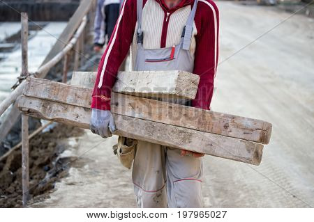Worker Carrying Wooden Beam