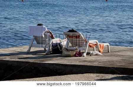 Occupied beach chairs on the city beach