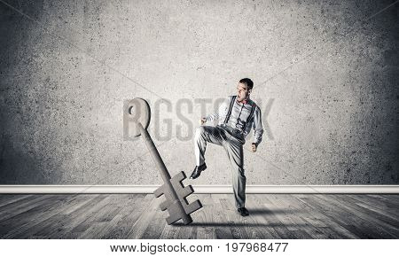 Determined businessman in concrete interior breaking with leg stone key figure. 3D rendering