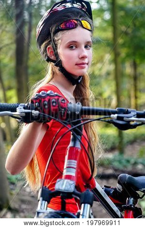 Bicycle child girl. Girl rides bicycle on green grass in park outdoor. Girl in bicycle helmet. Bicycle is good for good mood. Portrait of a cyclist.