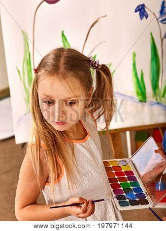Children painting on easel. Girl with boy learn paint in class school. Child picture on background. Portrait of a student, top view.