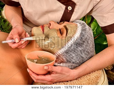 Collagen face mask. Facial skin treatment. Elderly woman 50-60 years old receiving cosmetic procedure in beauty salon. Professional beautician removing wrinkles. Mask against sagging skin.