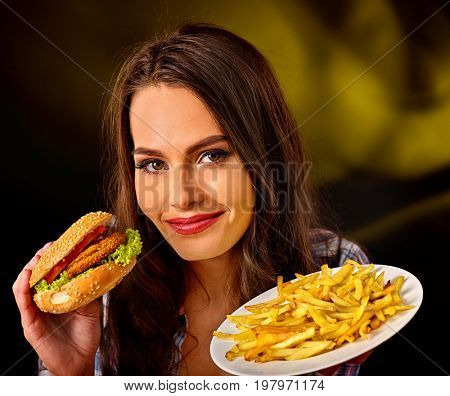 Woman eating french fries and hamburger. Portrait of student consume fast food on table. Girl trying to eat junk. Advertise fast food on dark background. Student eats semi-finished products.