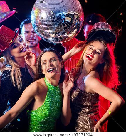 Dance party with group people dancing. Women and men have fun in night club. Happy girl on foreground and disco ball on background. Guys took off their hats. Opening a new strip club.
