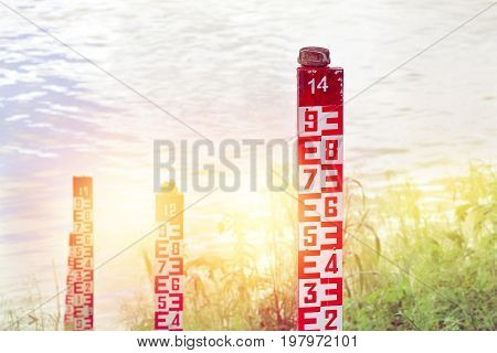 water level marker with numbers at a river in sunlight.