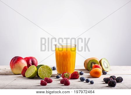 Fruit juice and various fruits on white table