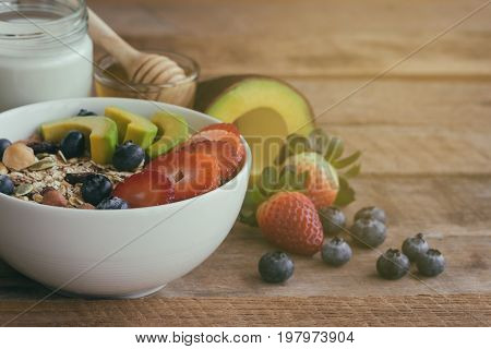 Muesli or granola on white bowl with fresh fruits nuts and cereal. Granola top with blueberries strawberries and avocado served with milk and honey for breakfast.Granola is healthy food for dieting.Start a day with granola and fresh fruits.
