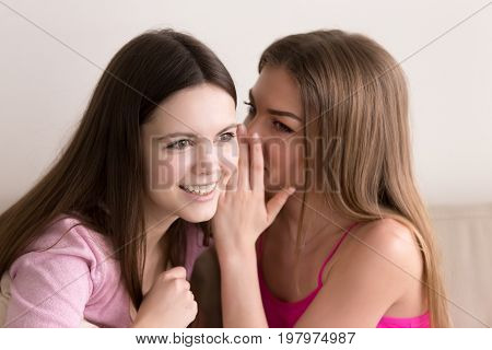 Headshot portrait of two young beautiful teen girls gossiping about boys. Attractive young ladies sharing their secrets, telling scandalous news, whispering in ear rumors and gossips, weave intrigues