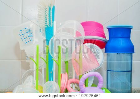 Close up colorful baby bottles drying on white plastic stand