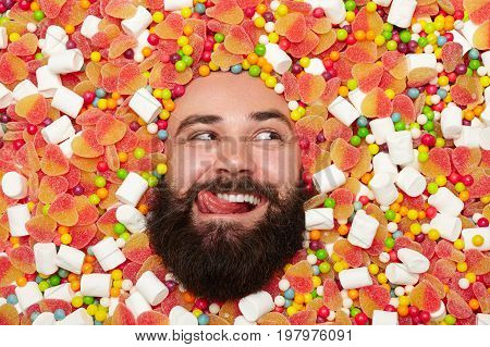 Young bearded man lying in candies and sweets and licking while looking away.