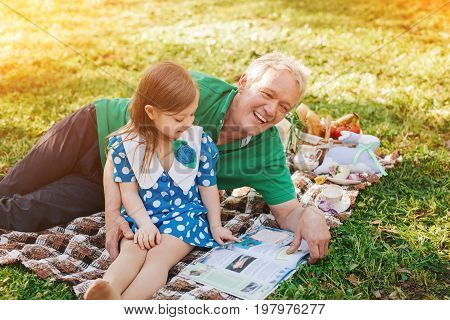 Little girl reading book with grandfather on plaid in park.