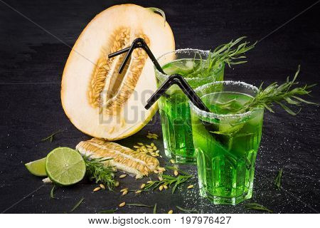A beautiful composition of alcohol beverages, lime and orange melon on a black background. Saturated green drinks in glasses with tarragon and black straws. Ripe and rustic cantaloupe and honeydew.