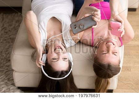 Close up portrait of two excited girlfriends enjoying music in headphones, making selfie photo with cellphone while lying on sofa at home. Teen girls having fun, singing popular hit together. Top view