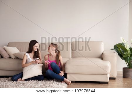 Two happy beautiful girlfriends in casual clothes and cellphones in hands sitting on carpet on floor in living room. Female friends relaxing and spending time together, browsing and chatting online
