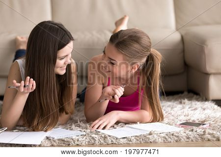 Two cheerful young teenager girls lying on carpet on floor and writing in notepads with pens. Female students studying at home, together preparing for exams, making wish lists, planning their future