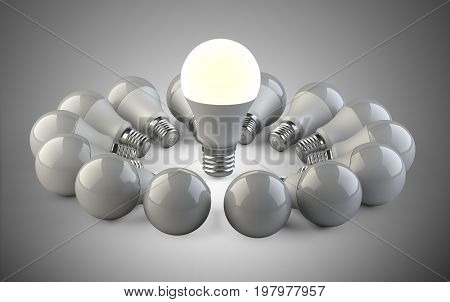 One glowing light bulb standing out from the unlit from lamps in the form of a circle. Leadership concept with bright ideas. 3d Illustration.