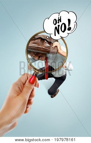 Job interview with manager in office. Concept of choose the best candidate. Female hand with magnifier. Frightened man does not want to get a job