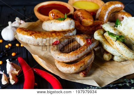 Sausage Assortment On Black Background Decorated With Garlic, Pe