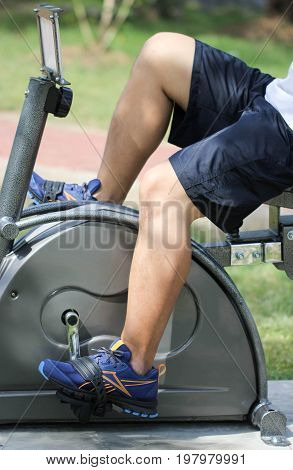 Close Up Asian Man Riding On Stationary Exercise Bike For Healthy In Public Park