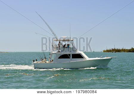 Sunset Key Florida Keys Florida USA - May 15 2017 : Fishing boat sailing past Sunset Key in Florida