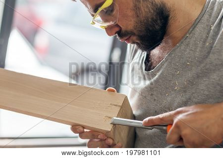 Man Treating A Wooden Product With A Chisel