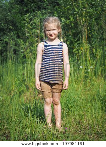 Dirty happy child standing on the grass. Bright sun summer heat. Girl in the sand