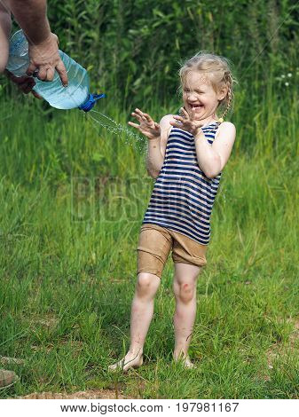 Dirty happy child. Male hand watered a little girl from the canister water. Laughing happiness splashing water. Summer heat nature