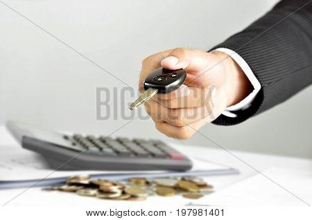 Businessman hand giving a car key - car rental & pawn concepts