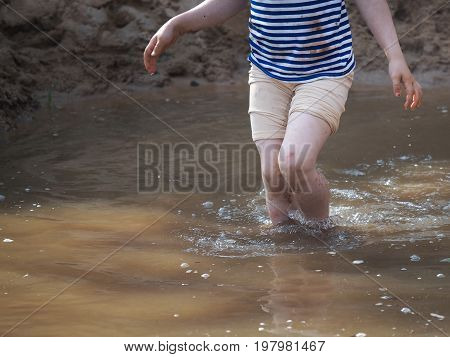 The baby's leThe baby's legs in the muddy water and sandgs in the muddy water and sand