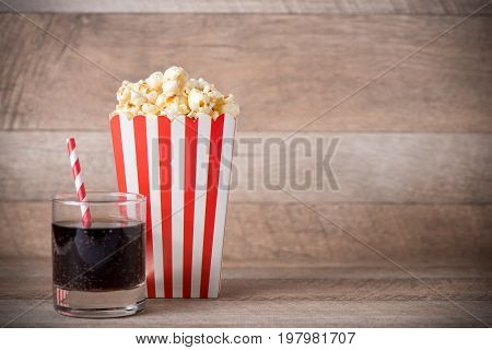 Popcorn In Red And White Cardboard With Soda On Wooden Table.