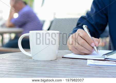 A man hand writing on notebook with coffee cup beside