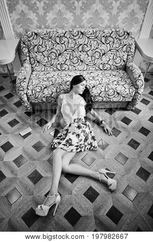 Portrait Of An Amazing Woman In Beautiful Dress Laying On The Wooden Floor. Black And White Photo.