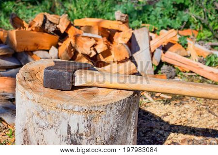 Great old hatchet against the pile of firewood. Concept - firewood for heating the journey into the wild. Background blur.