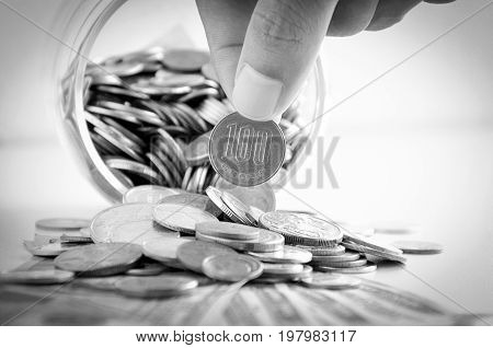 Hand picking up 100 Japanese yen (JPY) coin out of multi currency pile of coins - monochrome effect