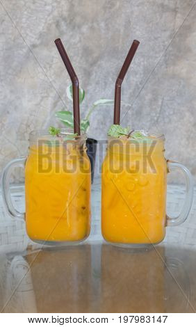 Orange juice with ice cube on glass table stock photo