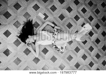Portrait Of A Stunning Young Woman In Gorgeous Dress Laying On The Floor With Her Smartphone. Black