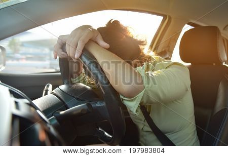 Tired Asian Business woman sleeping while driving a car with bad traffic jam on rush hours. Illness exhausted disease for overtime working concept.
